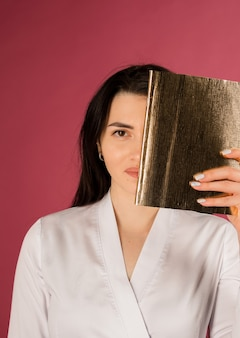 Beautician in a white uniform covered half of her face with a notepad on burgundy