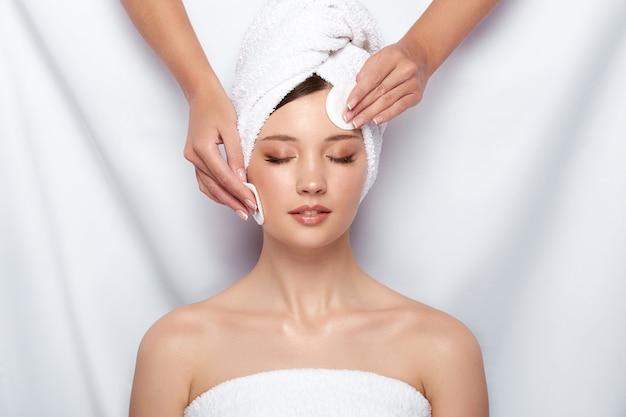 화장 솜으로 여자의 얼굴을 닦는 미용사