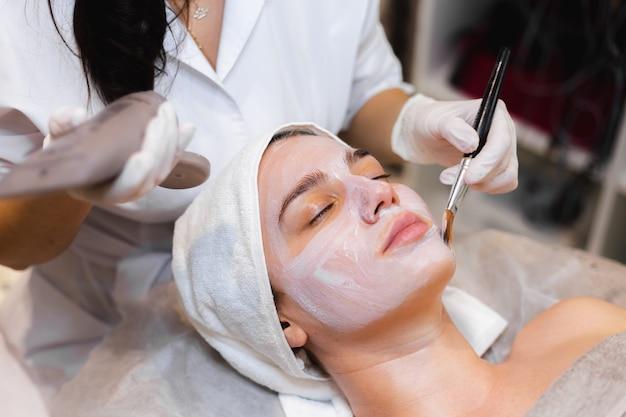 Косметолог с кисточкой наносит белую увлажняющую маску на лицо молодой девушки-клиента в спа-салоне красоты
