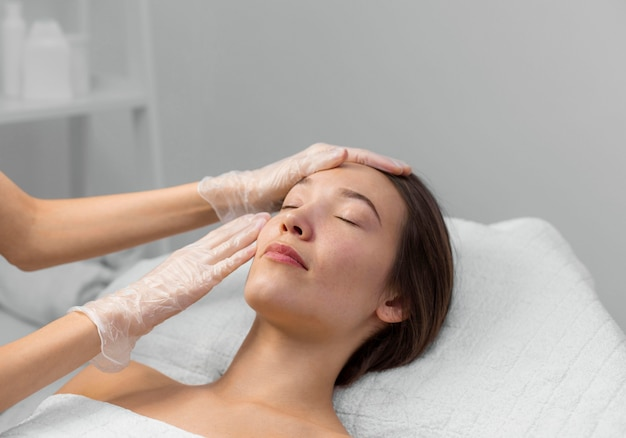 Beautician with female client at salon for face care routine