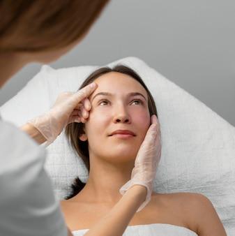 Estetista con cliente femminile al salone per la routine di cura del viso