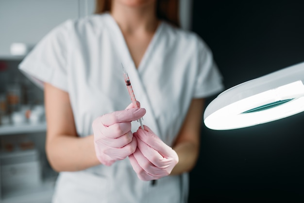 Beautician with syringe in hands, botox injection