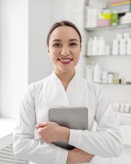 Женщина-косметолог в клинике с планшетом