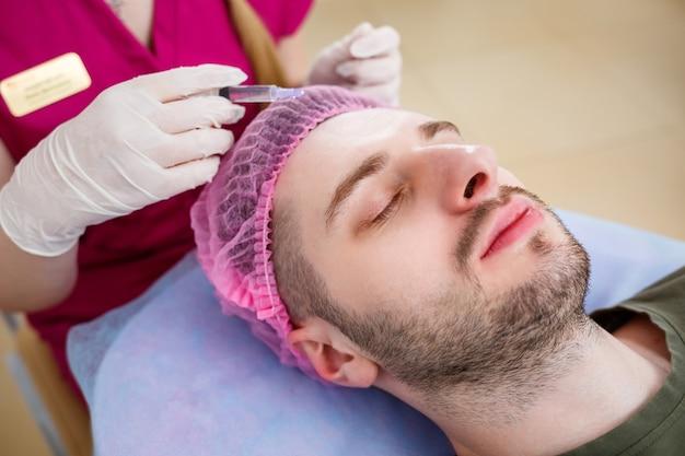 クリニックで若い男性のために超音波顔の洗浄手順を行っている美容師の女性。クローズアップと手のクライアントの肖像画、クローズアップの側面図。ビューティーサロンでの手続き。