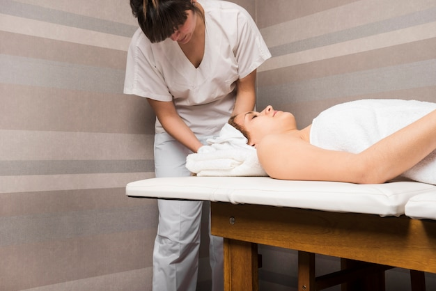Beautician wrapping towel on woman's head