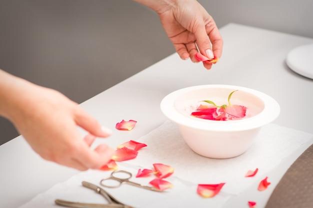 스파 테이블에 빨간색과 분홍색 장미 꽃잎과 매니큐어 목욕을 준비하는 미용사 여성 손