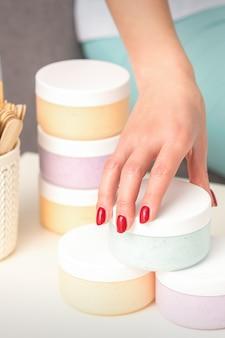 미용사 손은 보습 화장품을 제공하고 판매하는 테이블에서 화장품과 함께 항아리를 가져옵니다.