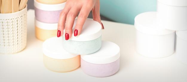 미용사 손에 화장품 보습 크림 왁스 페이스트를 제공하고 판매하는 테이블에서 화장품 병을 가져옵니다.