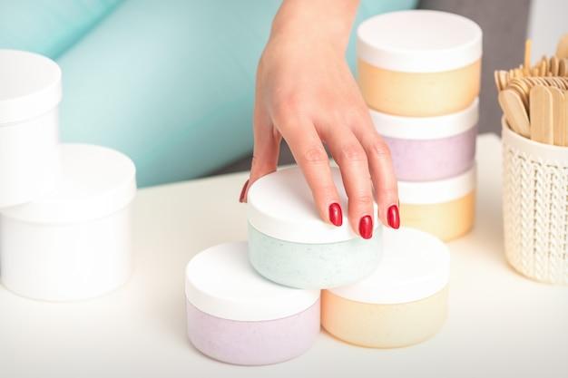 미용사 손은 화장품을 제공하고 판매하는 테이블에서 화장품으로 항아리를 가져옵니다.