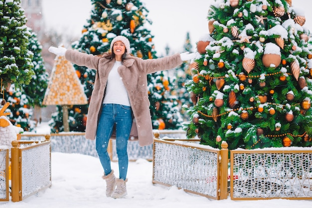 Beautidul woman near christmas tree in the snow outdoors
