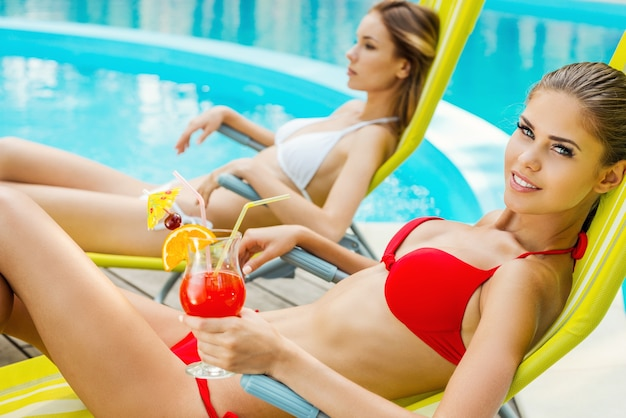 Красавицы у бассейна. вид сбоку двух красивых молодых женщин в бикини, пьющих коктейли во время отдыха в шезлонге у бассейна