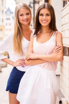 스타일의 아름다움. 야외에서 서로 가까이 서 있는 동안 카메라를 보며 웃고 있는 두 명의 아름다운 젊은 잘 차려입은 여성