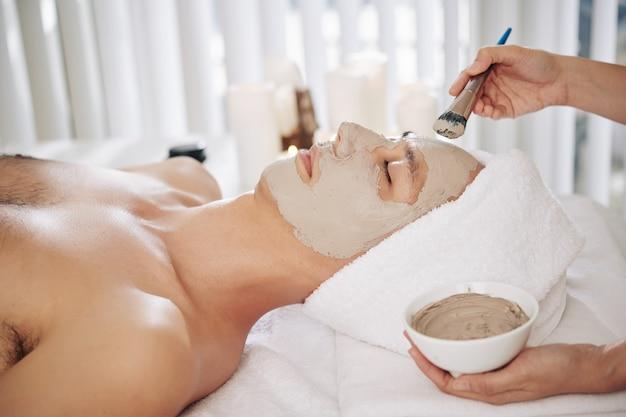 Beautifcian applying mud mask
