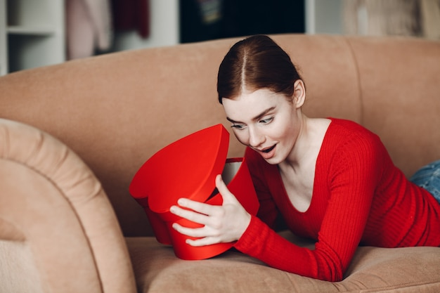 Beautifil young woman with red hair lying in her sofa in living room and holding and open the gift box in the shape of heart and smile. valentines day or birthday