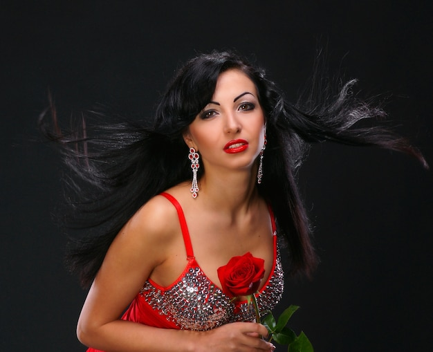 Beautifil young woman with a rose on dark background