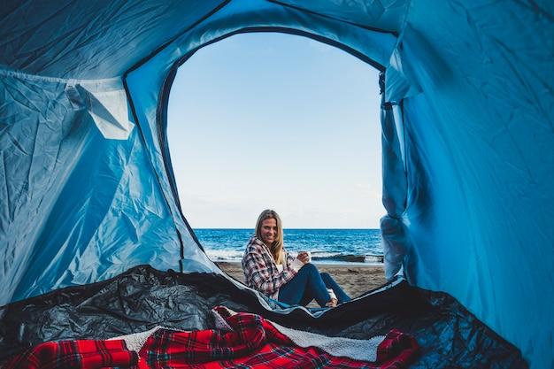 Красивая веселая блондинка улыбается, глядя изнутри палатки, разбитой лагерем на пляже прямо на песке