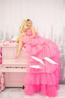 ピンクのピアノでポーズをとるbeautifulblonde女性。高品質の写真