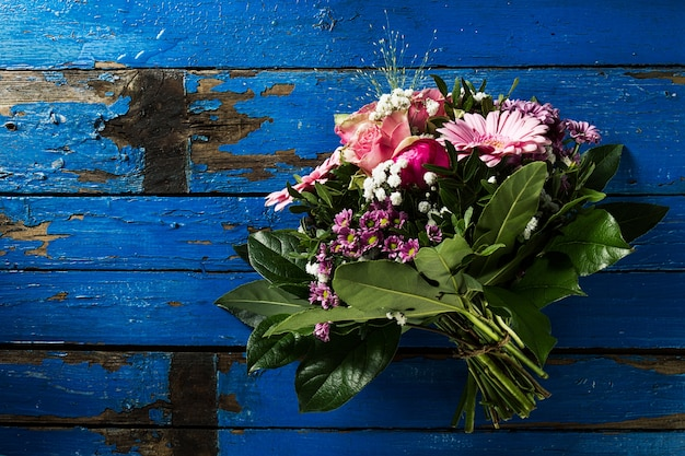 Beautifu pastel colors bouquet on blue rustic old table. top view.