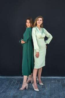 아름다운 녹색 드레스를 입고 자연 속에서 여름에 포즈를 취하는 아름다운 2명의 소녀. 여성 초상화