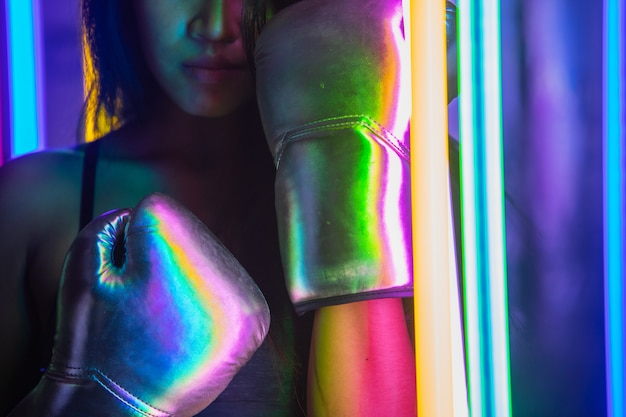 Beautiful 20s asian woman punch, poses with silver gold mitts gloves. office girl exercise between modern multi color fashion neon muay thai boxing gym with sweat water splash