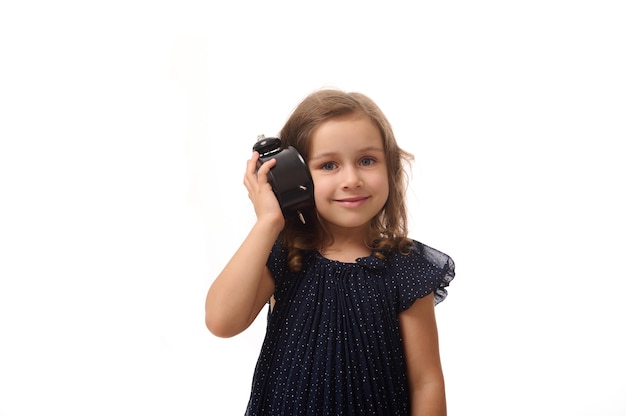 A beautiful 4 years old little girl in a dark blue dress holds an alarm clock near her ear and listens attentively to the sound, smiles looking at camera, isolated on white background with copy space