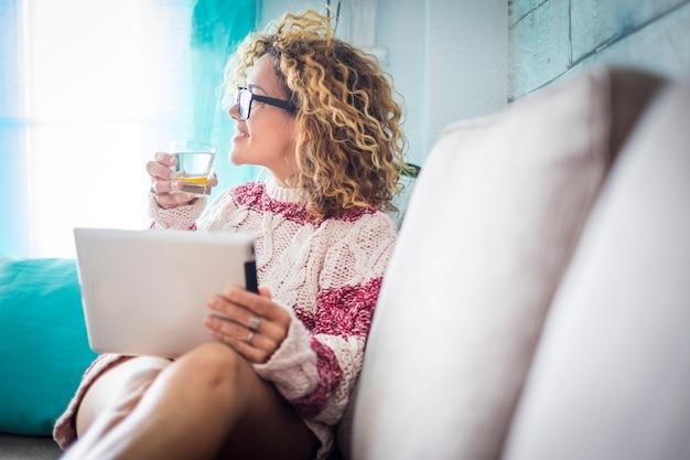 美しい 40 歳の中年女性 cacuasian 巻き毛の長い髪を自宅でタブレットで作業している 窓の外の白い外観