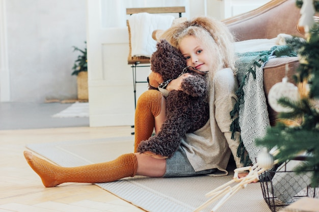 The beautiful 8 year old girl hugs toy bear and looks at the camera