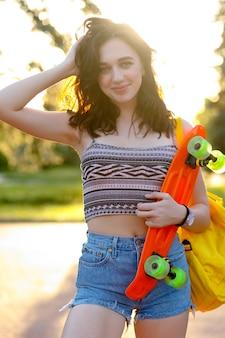 긴 머리에 긴 머리, 파란색 데님 반바지, 세련된 분홍색 운동화를 일몰 배경에서 포즈를 취한 아름다운 활동적인 브루네트 소녀. 녹색 바퀴가 달린 오렌지 스케이트를 들고 있는 소녀.