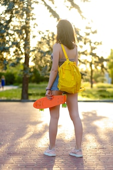 Beautiful active brunette girl with wearing top, blue denim shorts and stylish pink sneakers posing on sunset background. girl holding a orange skate with green wheels. girl is standing with her back