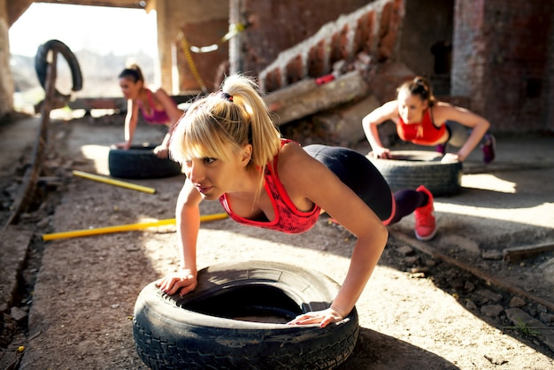 Beautiful active girls are doing push ups on tires in the old hangar.