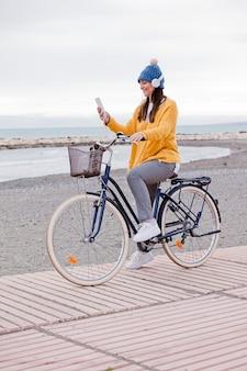 Красивая активная зрелая женщина с велосипедом на дороге у моря. счастливая улыбающаяся женщина средних лет с наушниками, слушающая музыку, копией пространства