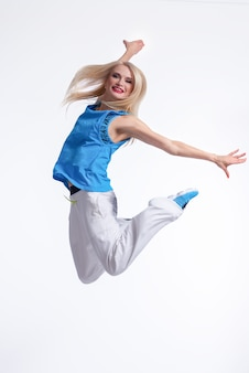 Beautiful active sportswoman jumping gracefully smiling on white
