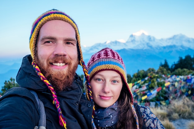 A beautiful and active woman and a bearded man do selfie in trekking in the mountains. the concept of active recreation and tourism in the mountains. trekking in nepal himalayas