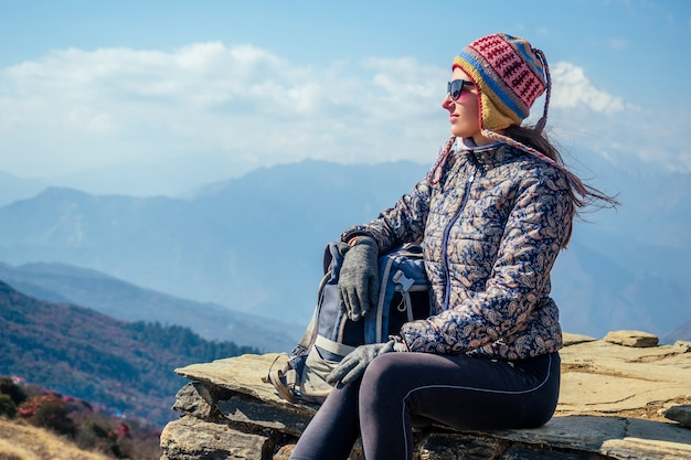 A beautiful and active woman in trekking in the mountains rests on the top. the concept of active recreation and tourism in the mountains. trekking in nepal himalayas