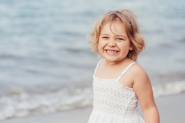 Beautiful adorable little girl natural face casual female portrait lifestyle beauty joyful girl on sea beach play. childhood concept