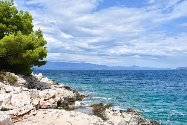 크로아티아, 흐 바르의 아름다운 아드리아 해. 녹색 소나무, 바위, 청록색 물