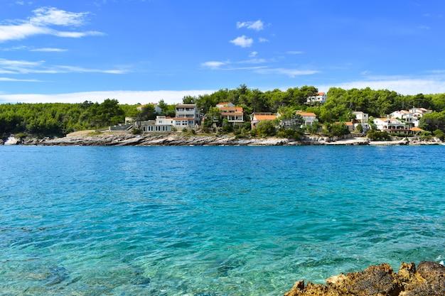 Красивое адриатическое море в хорватии. бирюзовая лагуна, дома в зеленых соснах, скалистый берег, ницца