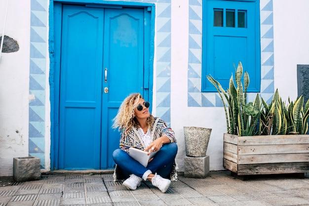 美しい大人の金髪の巻き毛モデルの女性は、彼女の代替ライフスタイルを楽しんでいる紙の本で床に座ります