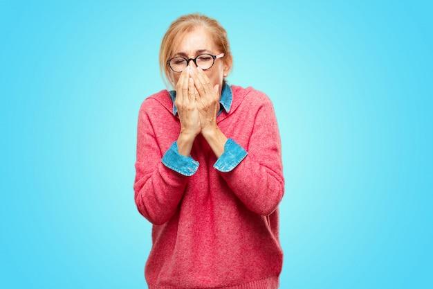 美しい大人のブロンドの女性咳、寒さやインフルエンザなどの冬の病気に苦しんで、気分