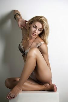 그녀의 속옷에 포즈를 취하는 아름 다운 성인 금발 여자.