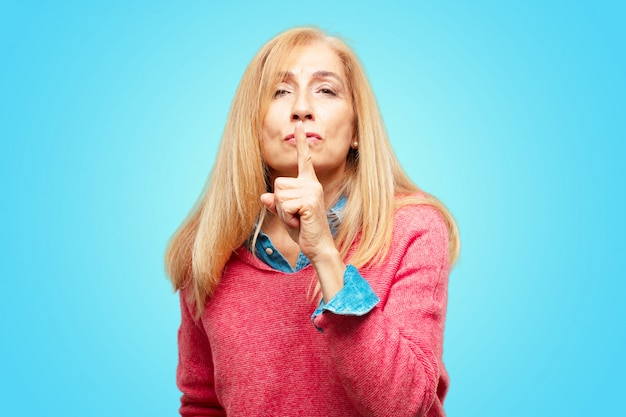 Beautiful adult blonde woman smiling, with index finger in front of mouth, requesting silence or sha