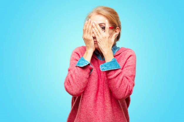 Beautiful adult blonde woman with a scared, frightened expression, covering eyes with both hands, pe