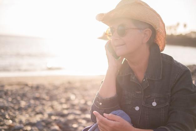 아름 다운 성인 백인 여자는 바다와 해변에서 전화로 말한다. 여름 연결 개념에 대 한 일몰 시간입니다. 자연과 기술을 즐기다