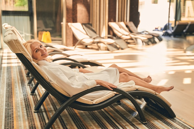 Beautiful adult caucasian woman relaxing in luxury indoors near the swimming pool in resort hotel