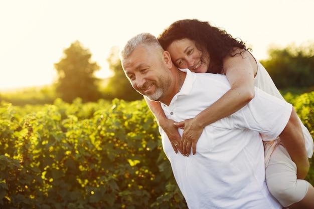 Красивая взрослая пара проводит время в летнем поле