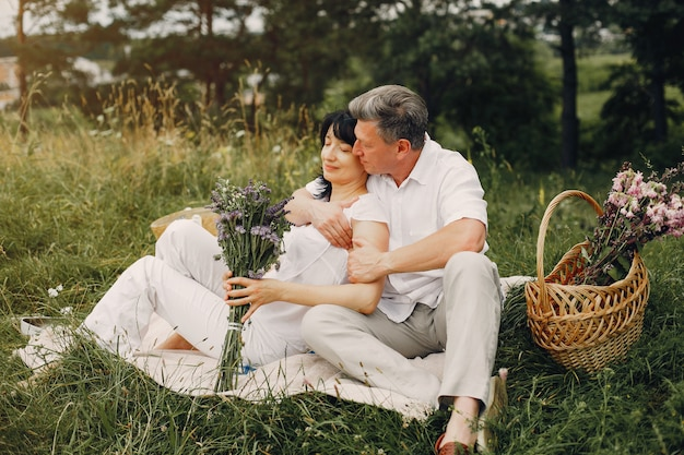 Beautiful adult couple spends time in a summer field