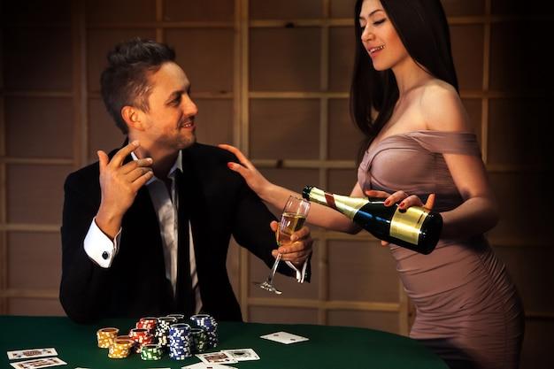폭락한 네크라인이 있는 노출 드레스를 입은 아름다운 성인 여성이 샴페인 포커 플레이어를 따르고 있습니다. 도박과 카지노의 개념에 따라