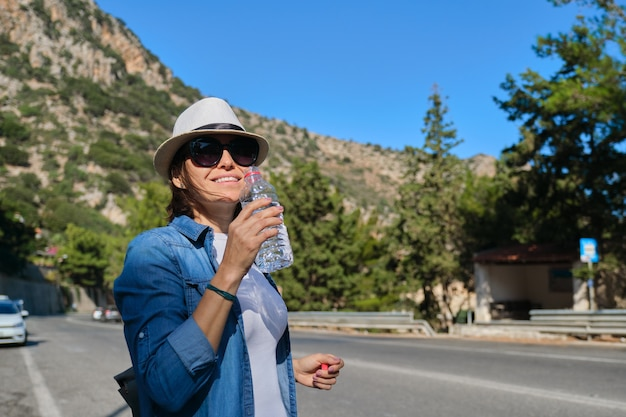 Beautiful adult female tourist removing thirst, drinking water from plastic bottle