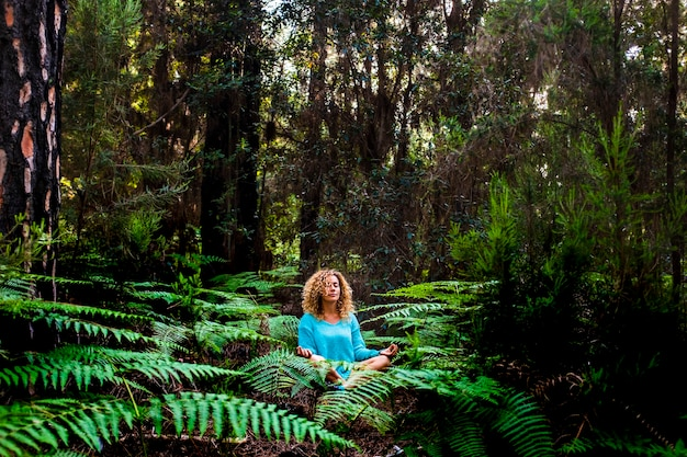 Beautiful adult lady do mindfulness meditation sit down in the silence of the green nature forest