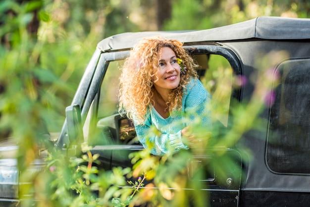 Красивая взрослая женщина среднего возраста улыбается и наслаждается счастьем с природой и лесом вокруг